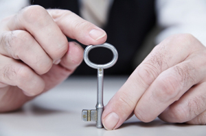 Photo of a business man holding a key